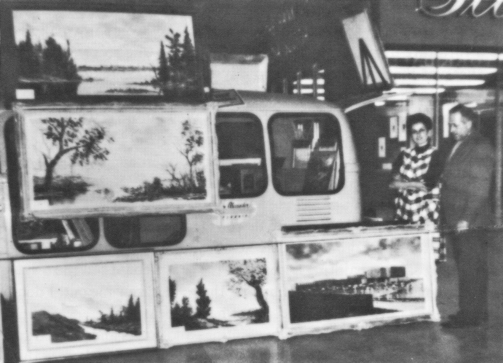 Bill and Margarete inside the shopping mall standing by their Volkswagen camper displaying Bill's paintings.
