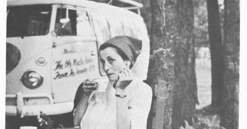 Photo of Margarete sipping tea during a roadside stop. Bill's Volkswagen bus is parked behind in a wooded area.
